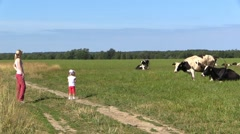 Girl and Mom Watch herd of cows on rural Field Stock Footage