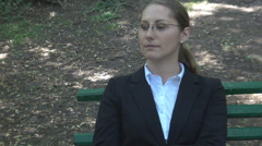 Business woman smoking while sitting on a bench in park, bad unhealthy habit Stock Footage