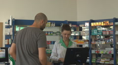 Ill patient discussing with woman pharmacist, pharmacist working searching pills - stock footage