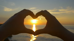 Capturing ocean sunset with heart shaped hands Stock Footage