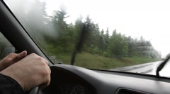 Hands holding steering wheel while driving through rain Stock Footage
