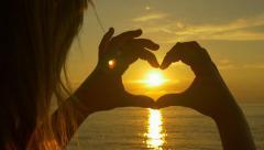 Sunset sun shining through heart shaped hands - stock footage