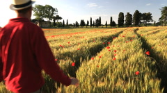 Poppy flowers barley Italian farmhouse male walking Tuscany Italy Stock Footage