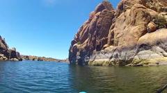 View Of Man Kayaking Past Huge Rock Face- Watson Lake Stock Footage