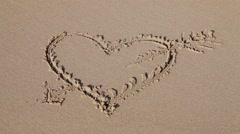 Love sign (heart with an arrow) written on sand - stock footage