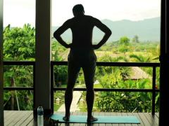 Man doing warm up exercise on luxury terrace with exotic view NTS Stock Footage