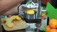 Street vendor squeezes juice from lemons Stock Footage