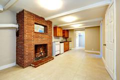 Empty basement room with brick fireplace Stock Photos