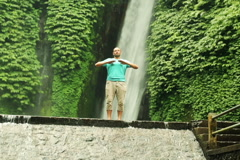 Man doing breathing exercise by waterfall, Bali, Indonesia NTSC Stock Footage