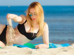 Summer vacation girl in bikini sunbathing on beach Stock Photos