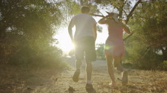 Happy couple holding brunches runs directed to the sun. 4K slow motion. Stock Footage