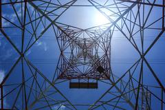 inside of a power pylon and look into the sun - stock photo