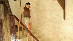 Woman talking on cellphone while walking in luxury home HD Stock Footage