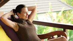 Woman with laptop relaxing on sofa at luxury terrace HD - stock footage