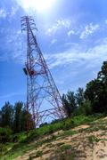 Power pylon with trees and blue sky and white clouds Stock Photos
