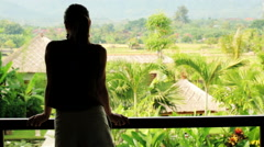 Woman relaxing, looking at beautiful garden from terrace HD - stock footage