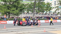 Rider climbs out of a Formula 1 car. G-Drive Show. 1280x720 Stock Footage