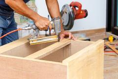 Carpenter used air-gun for make new furniture Stock Photos
