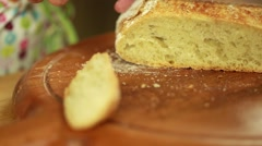 Woman cuts through fresh artisan bread Stock Footage