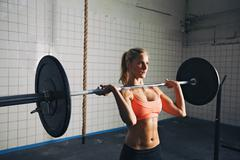 Strong woman lifting weights in crossfit gym Kuvituskuvat