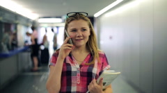Young teenager talking on cellphone, walking in tunel HD Stock Footage
