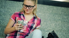 Cute teenager listen to the music on smartphone in shopping mall HD Stock Footage