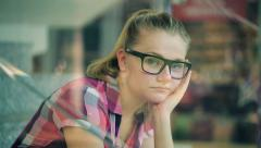 Sad, pensive teenage girl sitting on stairs in shopping mall HD Stock Footage