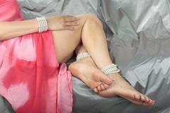 Woman legs wearing pink dress over grey satin fabric Stock Photos