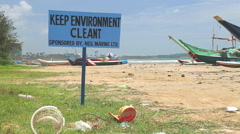 The view of polluted beach with a sign to keep environment clean. Stock Footage