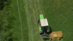 AERIAL: Flying above the tractor cutting grass Stock Footage