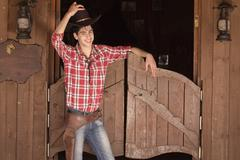 Cowboy in hat standing near saloon entrance Stock Photos
