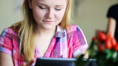 Cute teenage girl with tablet computer sitting in cafe HD Stock Footage