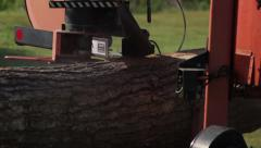 Portable sawmill cuts through log CU side shot - stock footage