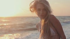 Gorgeous young girl with a beautiful figure in  swimsuit near the sea at sunset - stock footage
