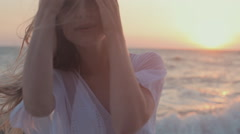 Young seductive girl with long hair in a white tunic stands at sunset near the Stock Footage