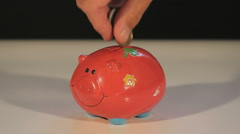 Filling a Piggy Bank with money, closeup Stock Footage