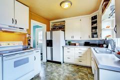 White kitchen interior with peach walls and khaki linoleum Stock Photos