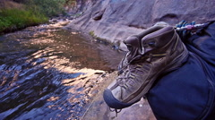 Hiker Boots on Backpack Next to a Wilderness Creek Stock Footage