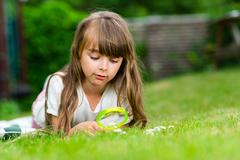 girl with loupe - stock photo