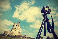 Camera on tripod with summer landscape with ruins, vintage retro style. Stock Photos