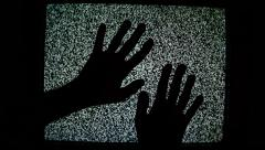 Male hands crawling up the TV screen with static television noise as background Stock Footage