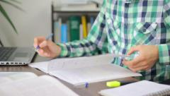 Clever college student writing in his notebook, doing homework, close-up - stock footage