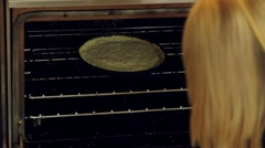 woman taking a berry fruit tart crust out of the oven - stock footage