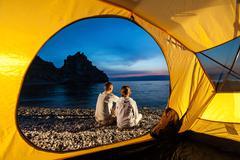Couple sits near tent Stock Photos
