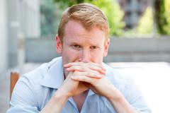 Closeup portrait, young man with hands clasped, in deep philosophical thought Stock Photos