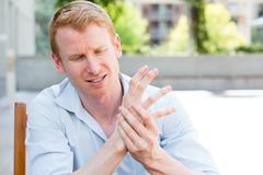 Closeup portrait, young man having acute bad joint pain in his hands Stock Photos