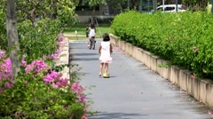 Children ride on scooters in park Stock Footage