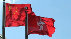 Hong Kong and People's Republic of China Flags flying against clear blue sky Stock Footage