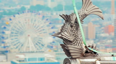 Japanese fish statue high above the city behind Stock Footage