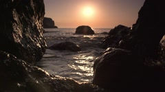 Stock Video Footage of Sunrise from the sea. Wave crashed into rocks in slow motion